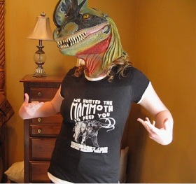 A woman wearing a dinosaur mask, wearing a T-shirt that reads