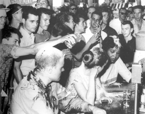 Protesters at a lunch counter sit-in at Woolworths in Little Rock, Arkansas, 1963, under assault from a white mob. The protesters were beaten, kicked, and burned with cigarettes. The assault lasted three hours, while police stood by.